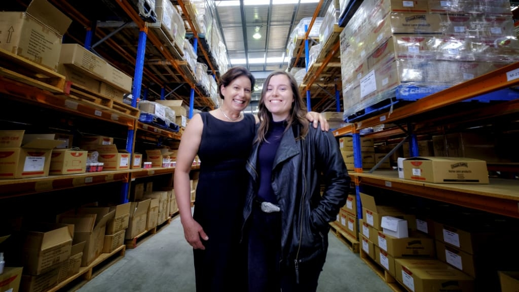Photo of Meryl and Holly with warehouse aisles on either side